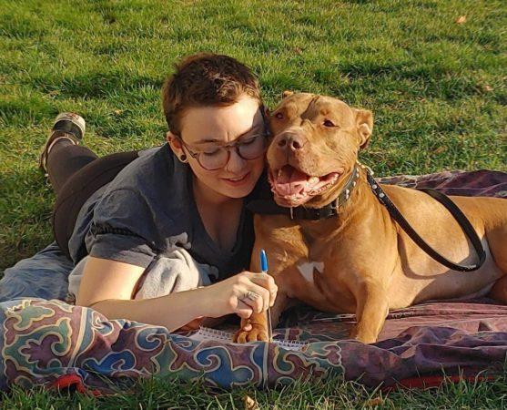 Étudiante couché sur le gazon avec son chien